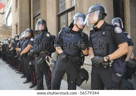 TORONTO-JUNE 25: Toronto Riot Police observe protesters at G20 Protest on June 25, 2010 in Toronto, Canada. - stock photo