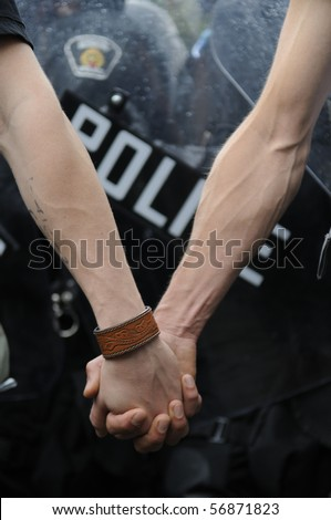 TORONTO-JUNE 26:  Two protesters holding their hands in front of riot police barricade during the G20 Protest on June 26, 2010 in Toronto, Canada.