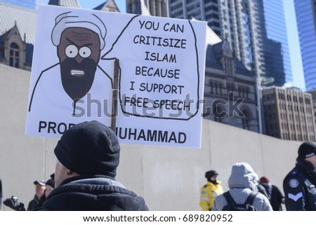 "TORONTO - March 4:  Anti Muslim supporters with signs mocking ""Prophet Muhammad"" during a pro and anti Muslim gathering on March 4, 2017 in Toronto, Canada."