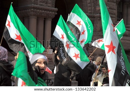 TORONTO - MARCH 16: Syrian demonstrators on March 16, 2013 in Toronto. Since March 2011, Syria has been embroiled in civil war in the wake of uprisings against Assad and the neo-Ba'athist government. - stock photo