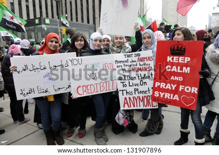 TORONTO-MARCH 16: Unidentified Syrian girls holding banners during a protest rally organized to raise awareness and commemorate two years of Syrian revolution on March 16, 2013 in Toronto, Canada.