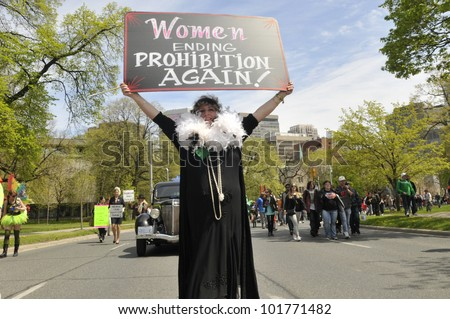 TORONTO- MAY 5: A Marijuana activist showing a sign which congratulates women in ending marijuana prohibition in Canada during the 14th annual Global Marijuana March on May 5  2012 in Toronto, Canada. - stock photo