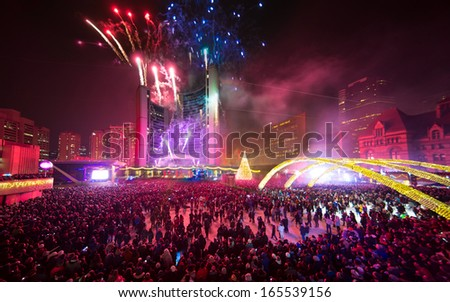 TORONTO - NOVEMBER 30: People watch the Christmas lights and fireworks at the Nathan Phillips Square in Toronto, Canada on November 30, 2013. - stock photo