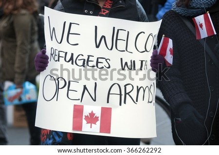 TORONTO - NOVEMBER 22: People with signs which has a Canadian Flag welcoming refugees from Syria during a solidarity rally to welcome Syrian refugees to Canada  on November 22, 2015 in Toronto,Canada. - stock photo