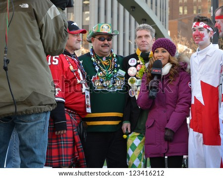 TORONTO - NOVEMBER 24: TV journalist interviews the sports fans during the 100th Grey Cup festival at  Nathan Philips Square on November 24, 2012 in Toronto.