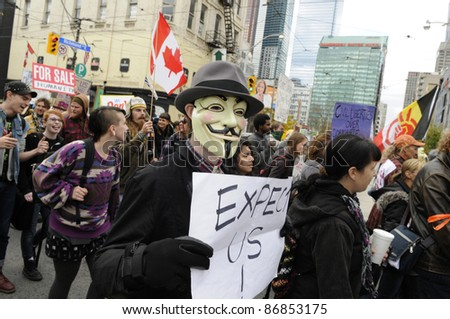 TORONTO - OCTOBER 17: Protestor wearing a guy fawkes masks walking in a rally  during the Occupy Toronto Movement on October 17, 2011 in Toronto, Canada. - stock photo