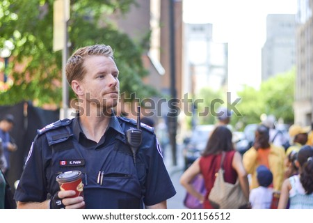 TORONTO, ONTARIO/CANADA - JULY 13: A cop walking by road on the day of 41st Annual Festival of India on July 13, 2013 in Toronto,Canada.  - stock photo