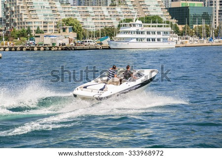 Toronto, Ontario, downtown, Aug.15, 2015, nice gorgeous amazing view of people driving motor boat on the lake Ontario at high speed on summer beautiful day - stock photo