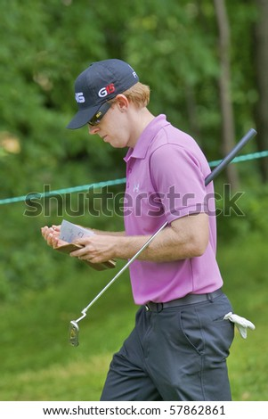 TORONTO, ONTARIO - JULY 21: U.S. golfer Hunter Mahan makes notes as he exits a green during a pro-am event at the RBC Canadian Open golf on July 21, 2010 in Toronto, Ontario - stock photo