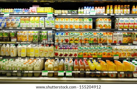 TORONTO - SEPTEMBER 14: Fruit juices shelf in a supermarket on September 14, 2013 in Toronto. In the US fruit juice can only legally be used to describe a product which is 100% fruit juice. - stock photo