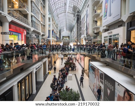 TORONTO - SEPTEMBER 19: Hundreds of customers wait for the door open at the Apple Store in Toronto, Canada on September 19, 2014. Apple's newest iPhones, the 6 and the 6 Plus go on sale this day. - stock photo