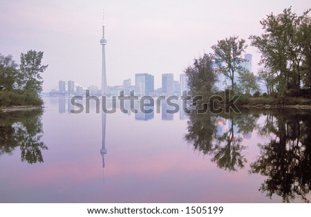 toronto skyline and lakeshore at a misty dawn from centre island - stock photo