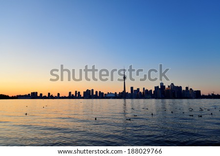 Toronto sunset silhouette at dusk over lake with urban architecture. - stock photo