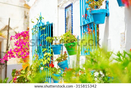 Torremolinos. Costa del Sol, Andalucia,Spain. Traditional White Village with flower pots in facades at Spain. Beautiful street decorated with flowers in Spain, tourism - stock photo