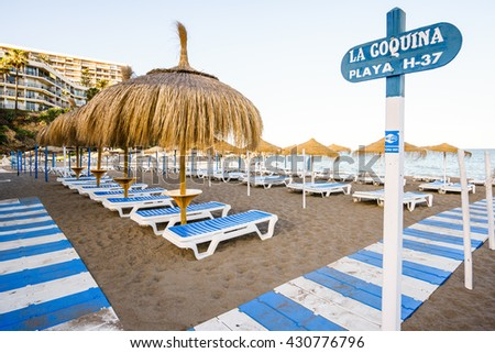 TORREMOLINOS,SPAIN - 25 MAY 2016:Beautiful beach with deckchairs and umbrellas against of blue sky - stock photo