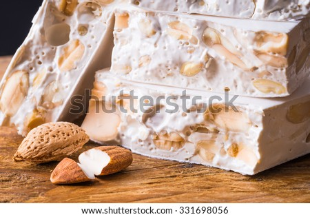 Torrone or nougat with nuts on wood background. - stock photo
