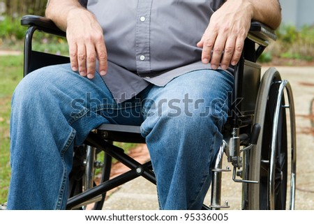 Torso and leg view of paraplegic man as he sits outside in his wheelchair.