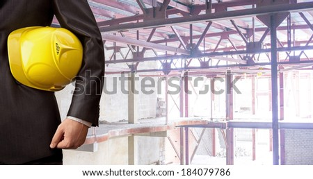 torso engineer hand holding yellow helmet for workers security against the support metal beams of the unfinished industrial concrete workshop or room inside Copy space for inscription