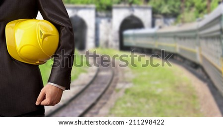 torso engineer or worker hand holding yellow helmet for workers security against the background of an underground mine with arc legs and rails for trolleys with coal in perspective - stock photo