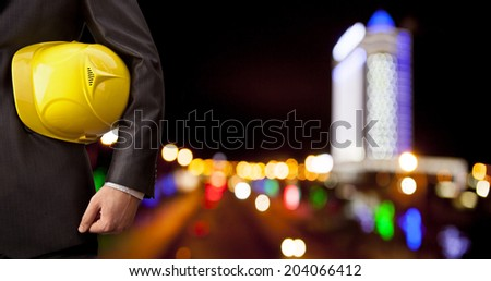 torso engineer or worker holding in hand yellow plastic helmet for workers security over  high-rise buildings and night road with bokeh light background - stock photo