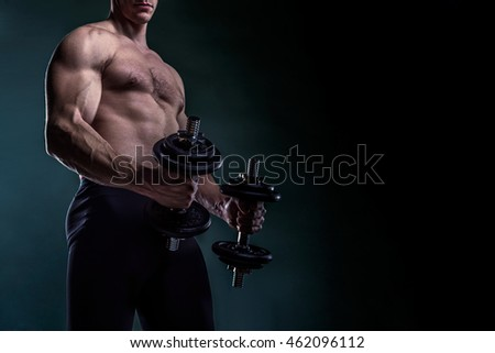 Torso of a Beautiful Bodybuilder Holding Dumbbells With Copy Space