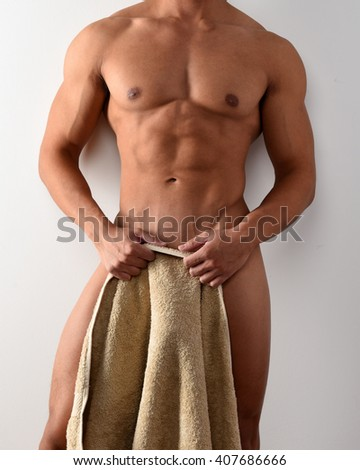 Torso of a muscular nude male holding a towel - stock photo