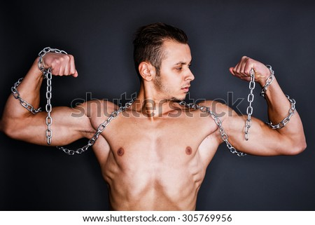 Torso of a muscular pumped man with chains around his neck and arms