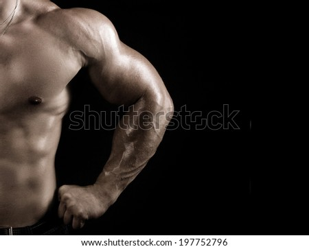 torso of a strong young man on dark background - stock photo