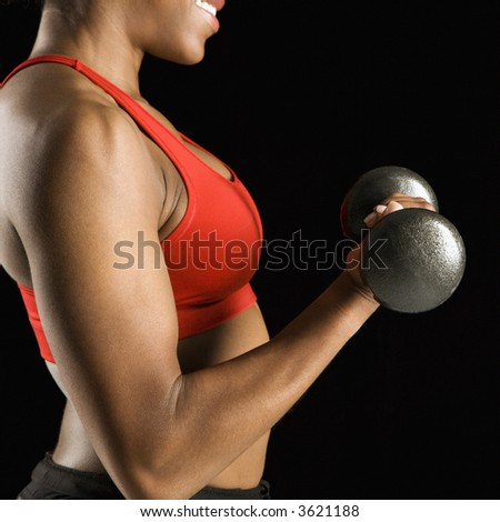 Torso of African American young adult woman lifting dumbbell. - stock photo