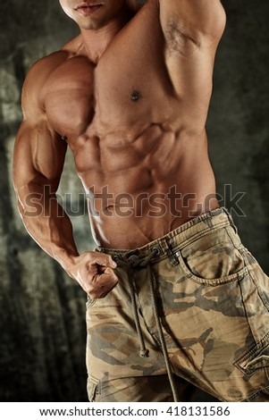 Torso of male bodybuilder posing flexing muscles. - stock photo