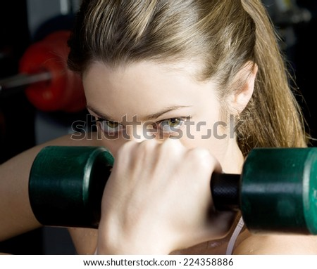 Torso of the beautiful woman is doing exercises with dumbbells in the sport club. - stock photo