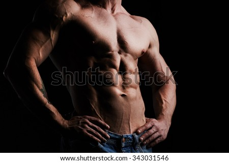 Torso of young muscular man - stock photo