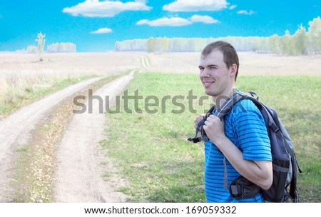 Torso portrait Young caucasian Man in blue shirt looking back and smiling on prairie country road on summer field or meadow and green forest background against day sunlight Copy space for inscription  - stock photo
