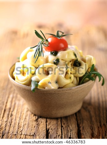 Tortellini with cheese sauce and arugula - stock photo