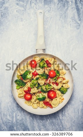 Tortellini with tomatoes and vegetables sauce in white frying  pan on gray wooden background, top view - stock photo