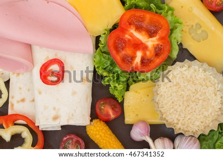 Tortilla and ingredients for her meat, tomatoes, rice, corn, peppers, tomato sauce