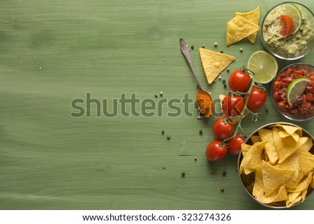 Tortilla chips arranged on wooden surface with guacamole and salsa - stock photo