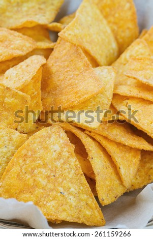 tortilla chips in basket on wooden surface - stock photo