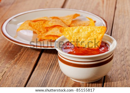 Tortilla chips in dish and salsa sauce  in bowl