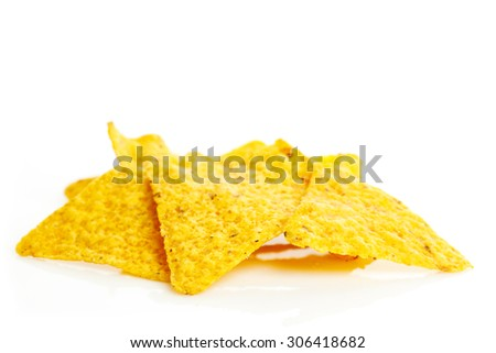 Tortilla chips on a reflective surface with a white background.