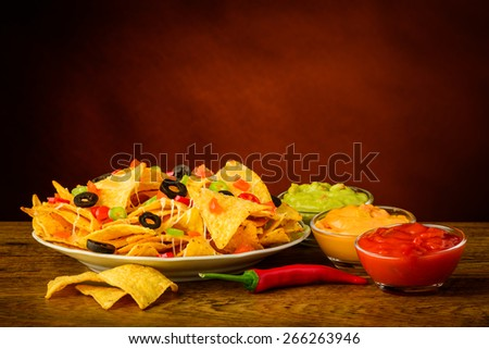 tortilla chips still life with salsa, cheese and guacamole dip