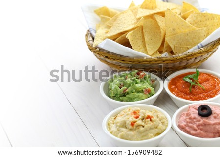 tortilla chips with four super bowl dips which are salsa roja, guacamole, taramasalata, and hummus. - stock photo