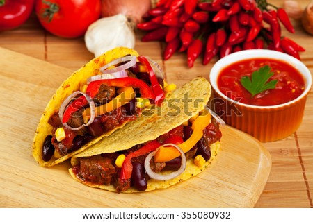 tortilla shells stuffed with meat sauce and beans  - stock photo