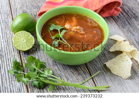 Tortilla Soup with Chips, fresh lime and cilantro on Rustic Wood Background - stock photo