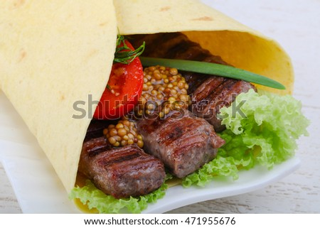 Tortilla with beef saucage, salad leaves and onion