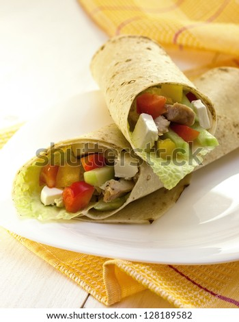 tortilla with chicken and vegetables on a white plate