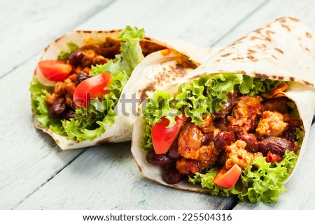 Tortilla with meat and beans on a table - stock photo