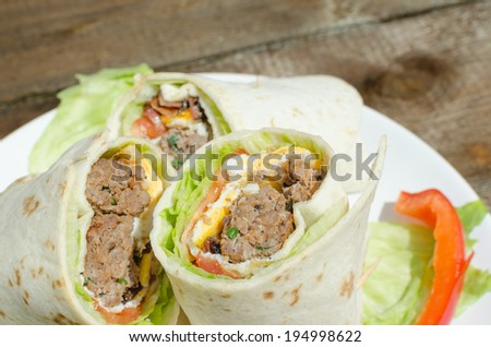 Tortilla with meat, eggs and bacon cut in the middle - stock photo