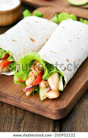 Tortilla wraps on cutting board on wooden table