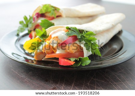 Tortilla wraps with fresh chicken, vegetables and garlic dressing on a plate